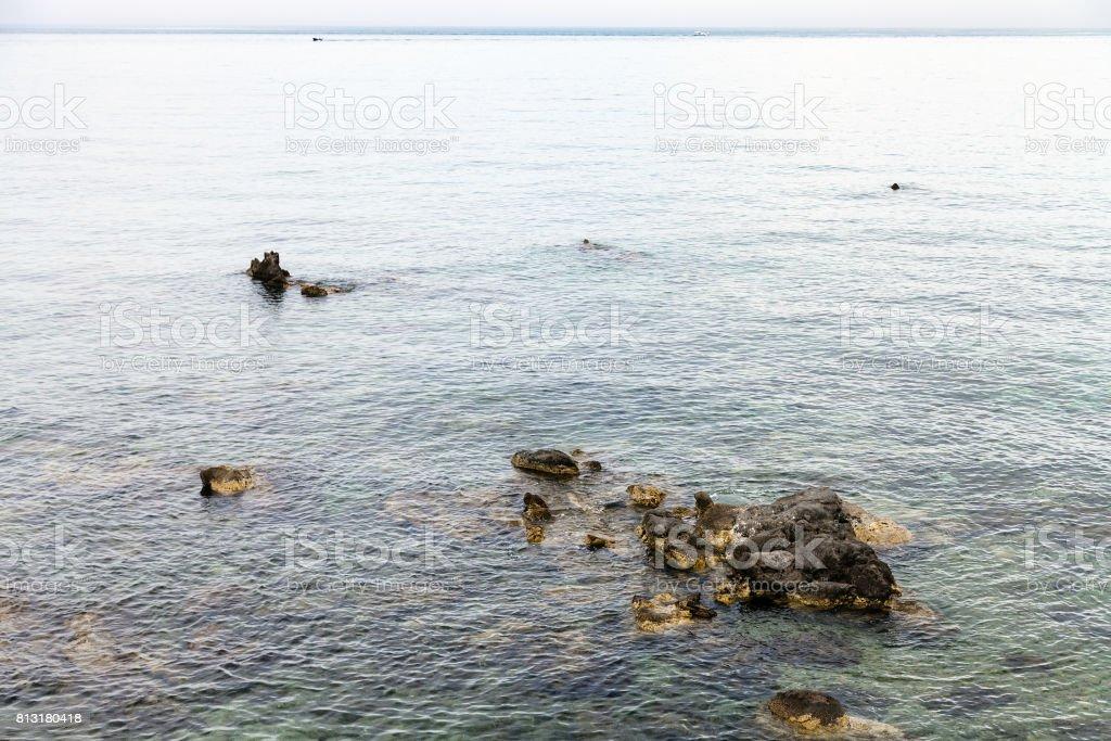 rocks in water near waterfront in Giardini Naxos stock photo