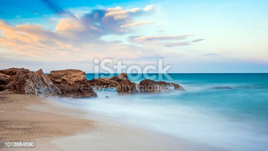Rocks on a sandy beach in Miami Platja, Catalunya, Spain. Copy space for text.