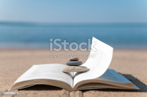 Book sitting on a beach with rocks stacked on top in a zen-like fashion.