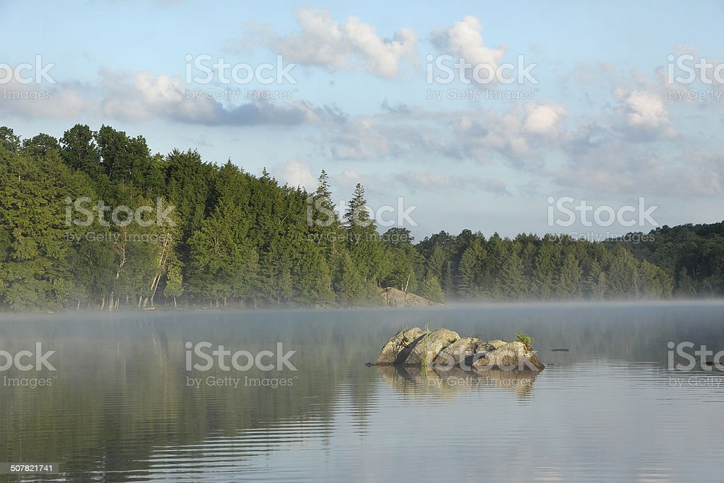 Rocks on Misty Lake stock photo