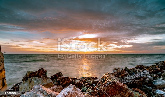 Rocks on stone beach at sunset. Beautiful beach sunset sky. Rocks on stone beach at sunset. Beautiful beach sunset sky. Twilight sea and sky. Tropical sea at dusk. Dramatic sky and clouds. Calm and relax life. Nature landscape. Tranquil and peaceful concept.