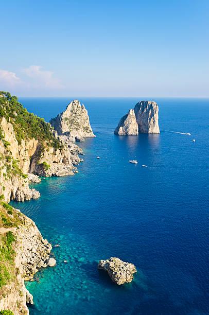 Rocks (Capri Island) Faraglioni rocks, near coast of Capri Island (Italy, Bay of Naples) rocky coastline stock pictures, royalty-free photos & images