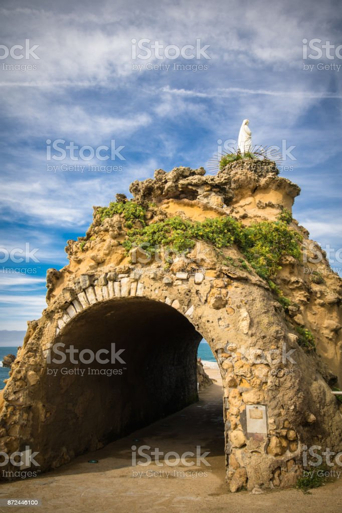 rocky arch passage of rocher de la vierge in beautiful scenic blue sky, Biarritz, Basque country, France stock photo