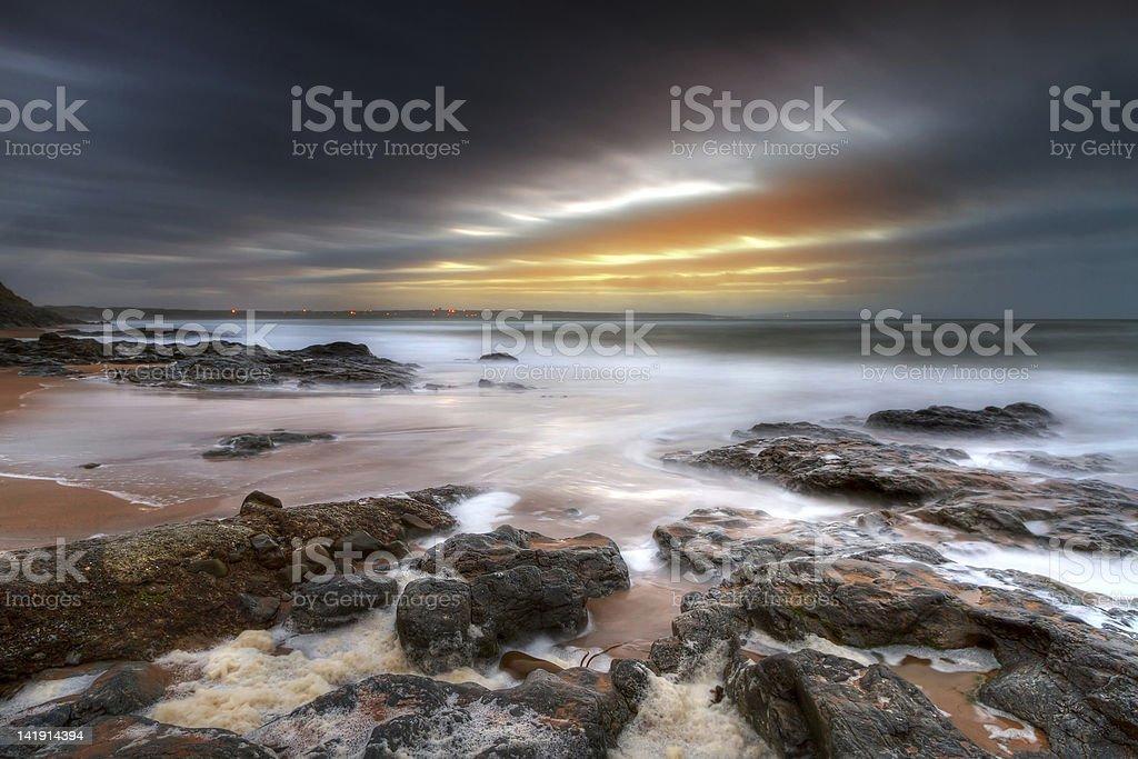Rocky Atlantic ocean beach at dusk stock photo