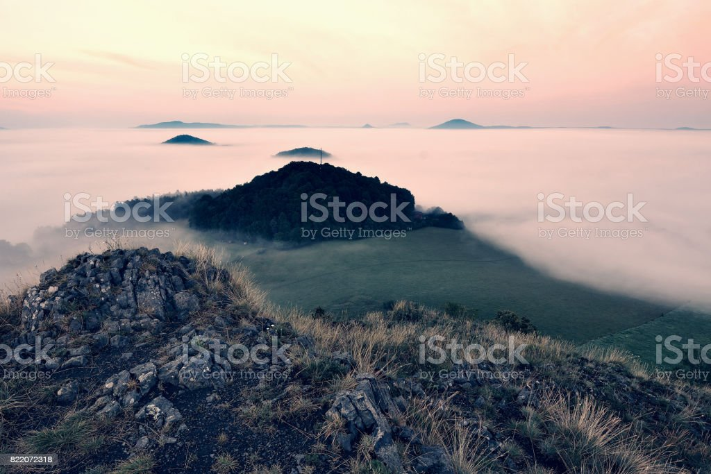 Rocky basalt peak on hill.   Forest valley full of gentle fog and Sun above heavy mist. stock photo
