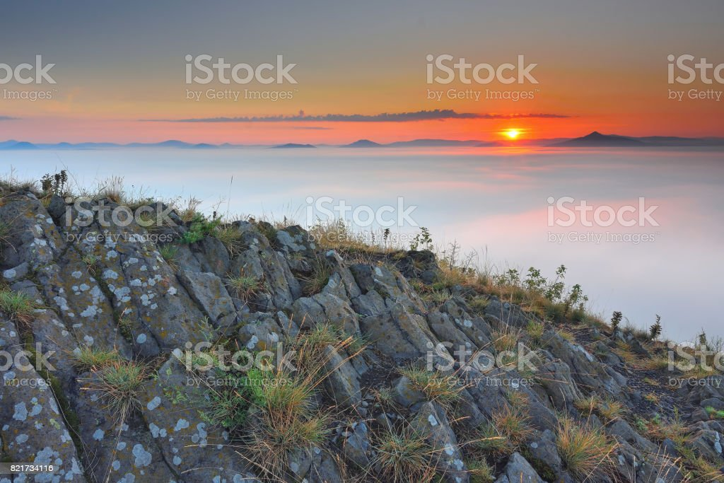Rocky basalt peak on hill.  Sharp peak of basalt formation. Long basalt poles of cold volcano. stock photo