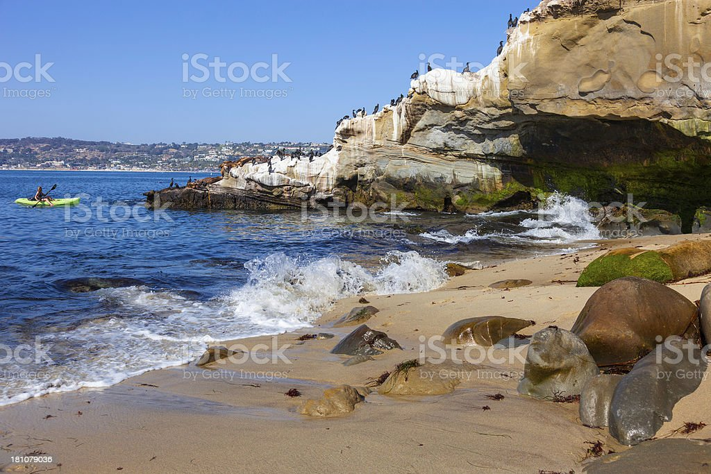 Rocky bay on the coast at La Jolla, and kayaker in the ocean stock photo
