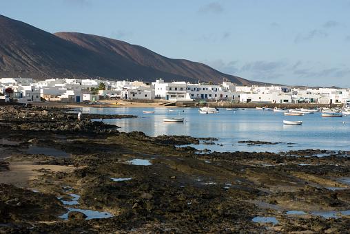 Rocky beach and white houses in La Graciosa Island. Caleta del Sebo.