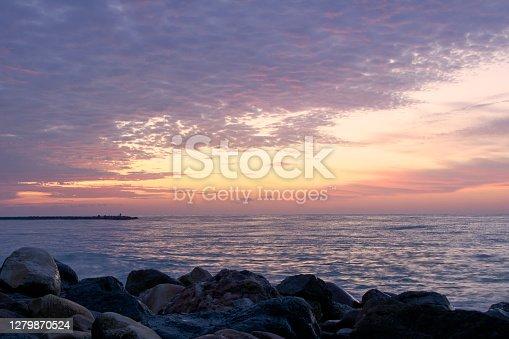 Rocky beach at sunrise, long exposure, foggy clouds