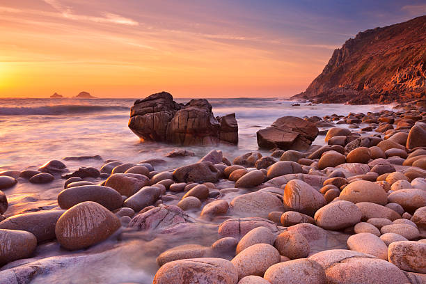 Rocky beach at sunset, Porth Nanven, Cornwall, England stock photo