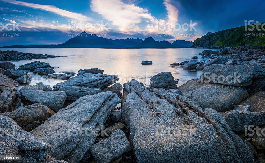 Rocky beach blue ocean sunset dramatic mountain peaks Highlands Scotland stock photo