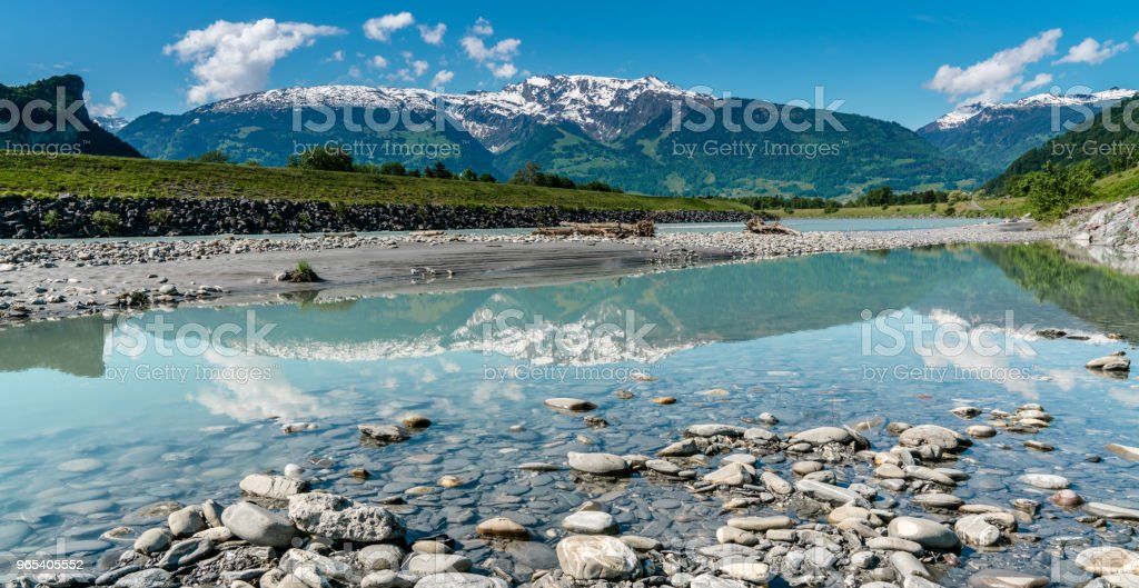 rocky beach on the banks of the Rhine with a mountain landscape reflected  in the foreground zbiór zdjęć royalty-free