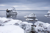 Rocky beach on wintertime. Evening light and icy weather on shore like fairy tale country. Winter on coast. Blue sky, white snow, ice covers the land on seaside. Waterside on Juminda, Estonia, Europe