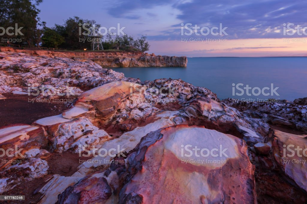 Rocky beach sunset with clouds stock photo