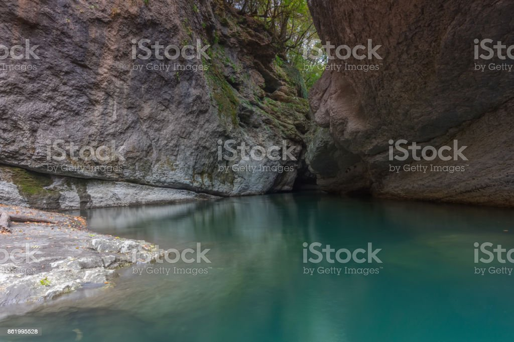 rocky canyon with a bluish green mountain river stock photo