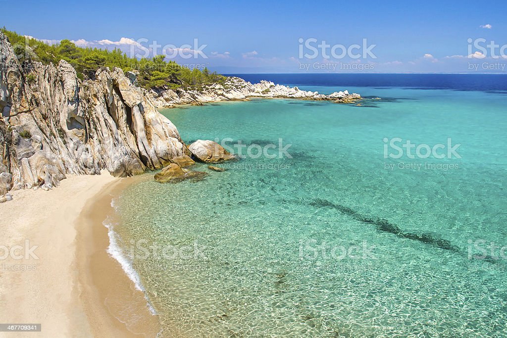 Rocky cliff above the beautiful clear water stock photo
