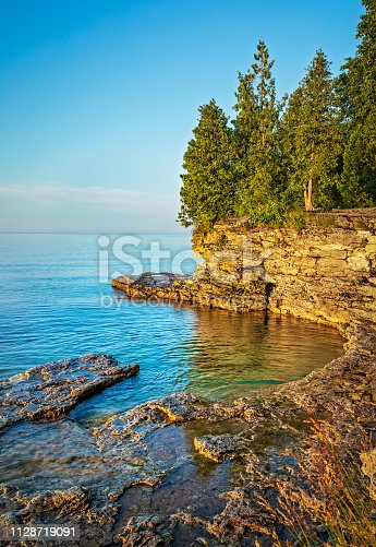 Early morning view of a rocky cliff on the coast of Lake Michigan from Cave Point Park in Door County Wisconsin.