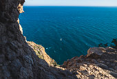 Rocky cliff with view on gull flying over the ocean in the natural park 'Serra Gelada' in Albir, Costa Blanca, Spain