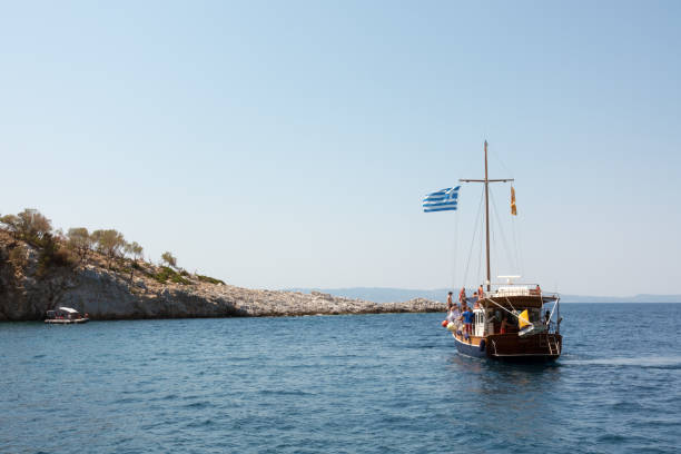 Rocky coast and tourist boat in Kelyfos islet, Neos Marmaras stock photo