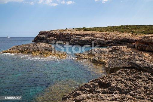 Türkisblaues Meer, blauer Himmel mit einigen Wolken, gelbe Felsen im Vordergrund