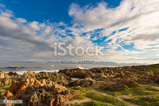 Rocky coast line on the ocean at De Kelders, South Africa, famous for whale watching. Winter season, cloudy and dramatic sky.