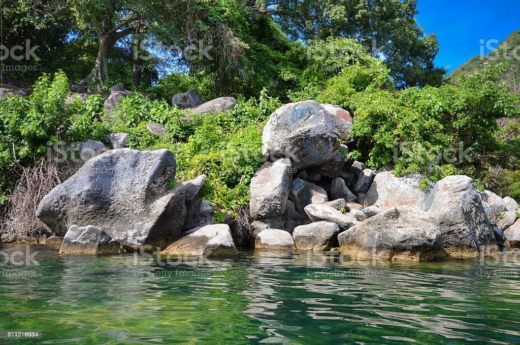 Rocky coast of the volcanic caldera Lake Coatepeque in Salvador stock photo