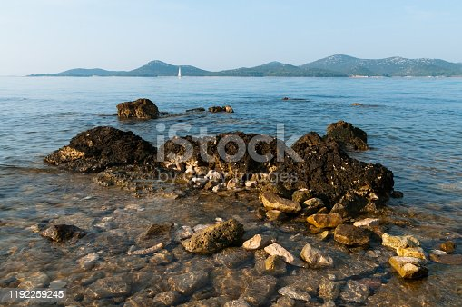 Rocky coast with a view of Adriatic Sea and island and boat from Biograd of Croatia, Europe.