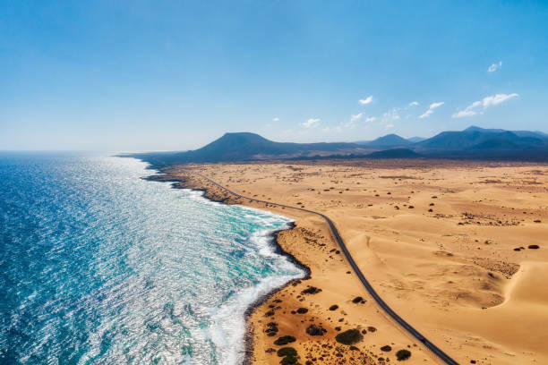 Rocky coastline and highway with golden sand and blue water stock photo