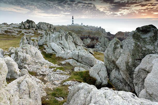 rocky coastline and lighthouse stock photo