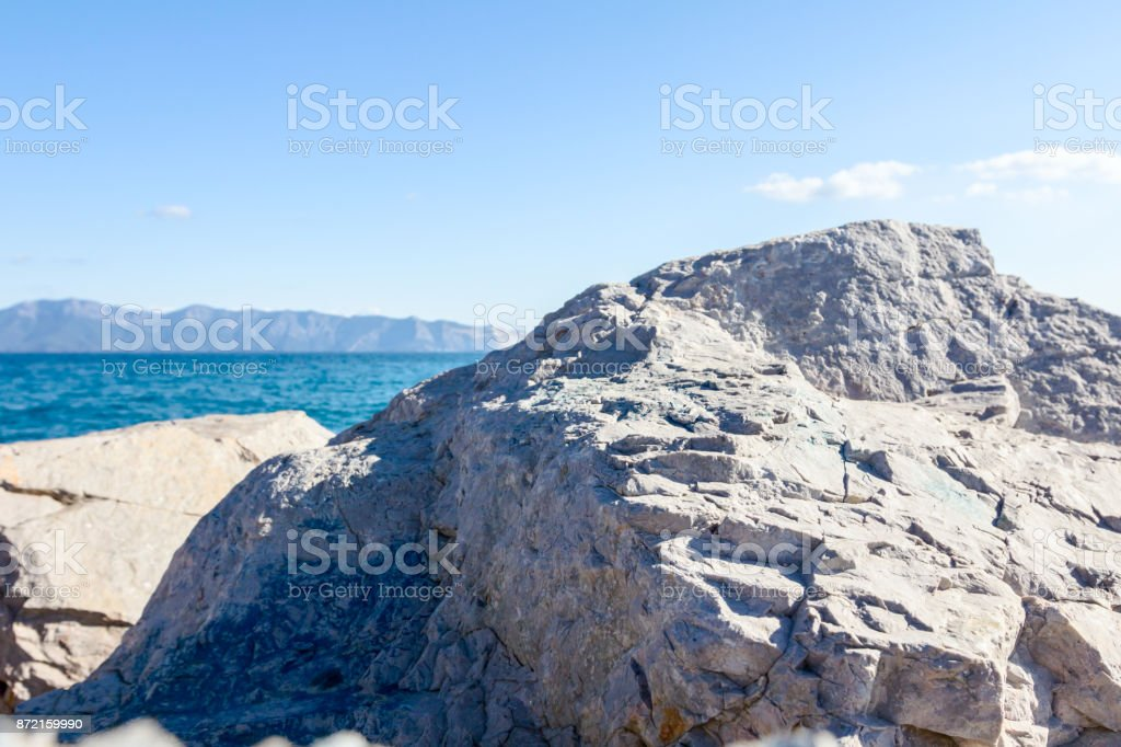 Rocky coastline, big stone is sticking out above the sea level stock photo