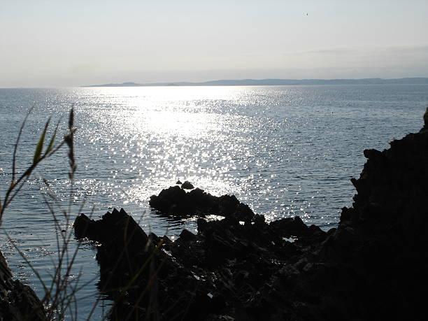 rocky coastline in glistering sun - fsachs78 stockfoto's en -beelden