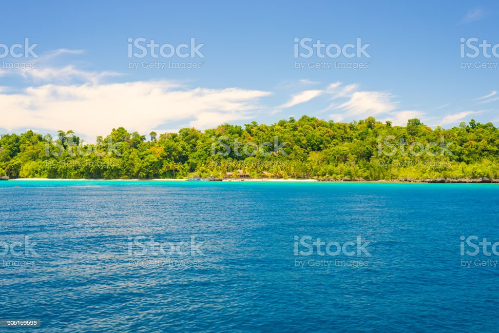 Rocky coastline of island spotted by islets and covered by dense lush green jungle in the colorful sea of the remote Togean Islands (or Togian Islands), Central Sulawesi, Indonesia. stock photo