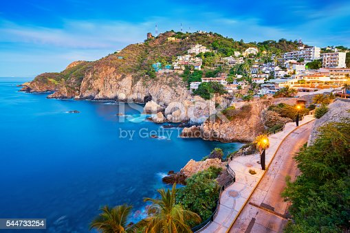 Photo of a rocky coastline with illuminated promenade and the Pacific Ocean in Acapulco, Mexico at dawn.