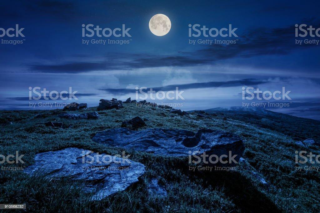 rocky formation on grassy hillside at night stock photo