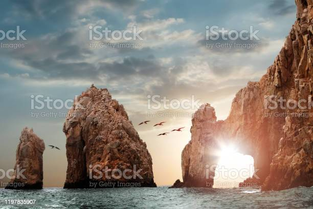 Photo of Rocky formations on a sunset background. Famous arches of Los Cabos. Mexico. Baja California Sur.