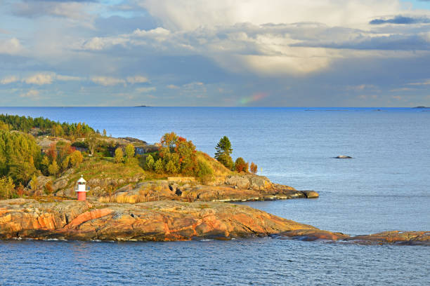 Rocky island with lighthouse of Helsinki archipelago at sunset. Distant rainbow in sea. Finland stock photo