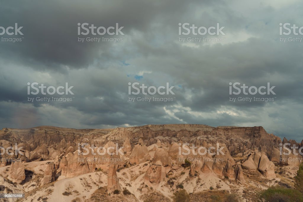 rocky landscape in cloudy weather, rain and sun in canyon