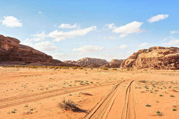 Rocky massifs on red sand desert, vehicle tracks ground, bright cloudy sky in background, typical scenery in Wadi Rum, Jordan stock photo