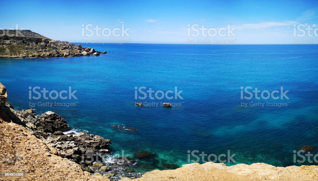 Rocky mediterranean seashore with azure and turquoise color water at Malta royalty-free stock photo