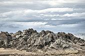 Rocky mountain coast, Kunashir island, Stolbchaty cape, cloudy gray gloomy sky.