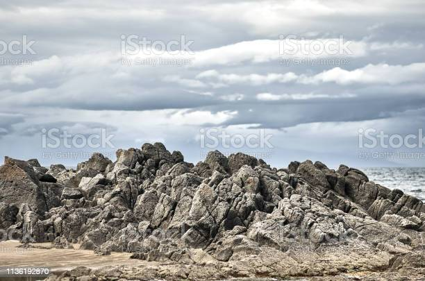 Photo of Rocky mountain coast, Kunashir island, Stolbchaty cape, cloudy gray gloomy sky.