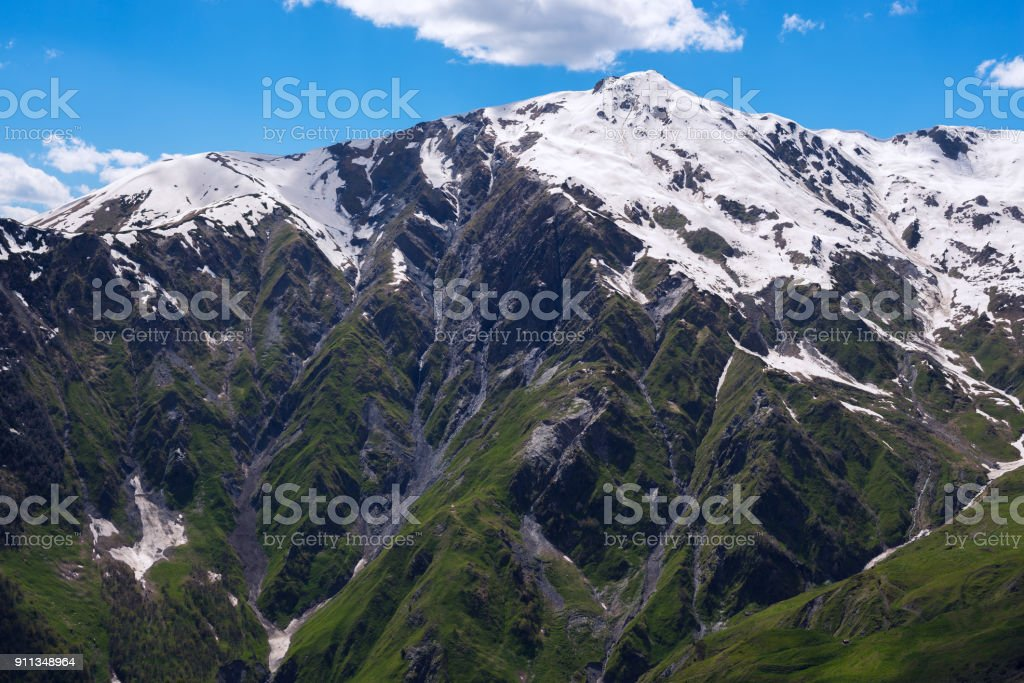 Rocky mountain range with snow-capped peaks and green slopes stock photo