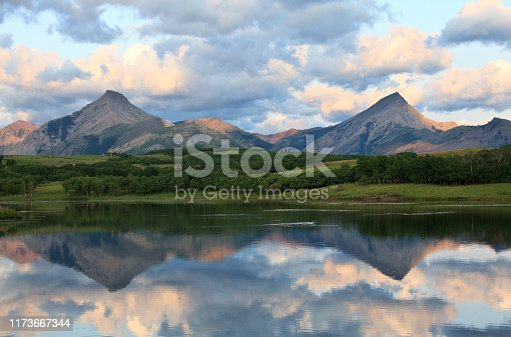 A moody scene of the Canadian Rockies reflected in a lake. Image taken near High River, Alberta, Canada.