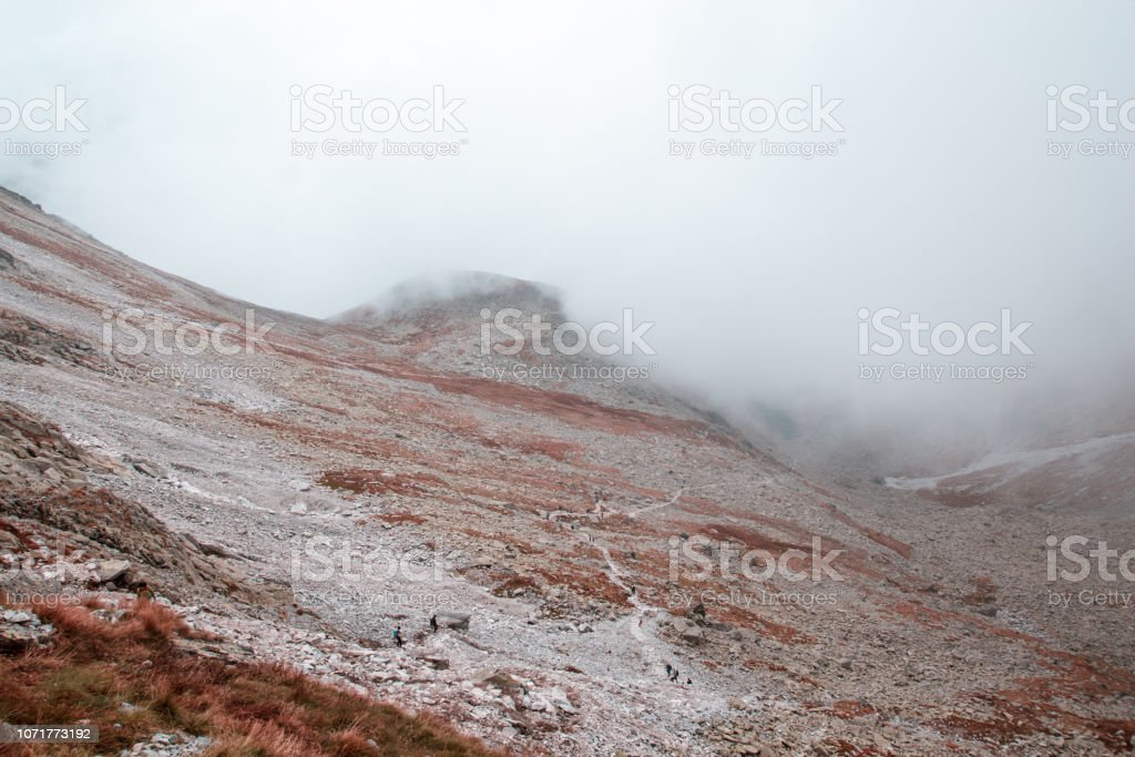 Rocky mountain valley covered with fog, below are hike small people