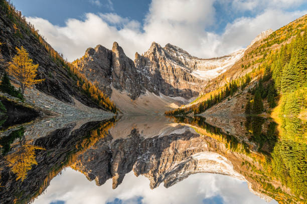 Rocky mountains in autumn forest reflection on Lake Agnes Tea House in Banff national park stock photo