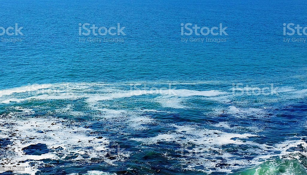 Rocky outcrop creates swirling eddies of water in calm sea photo libre de droits