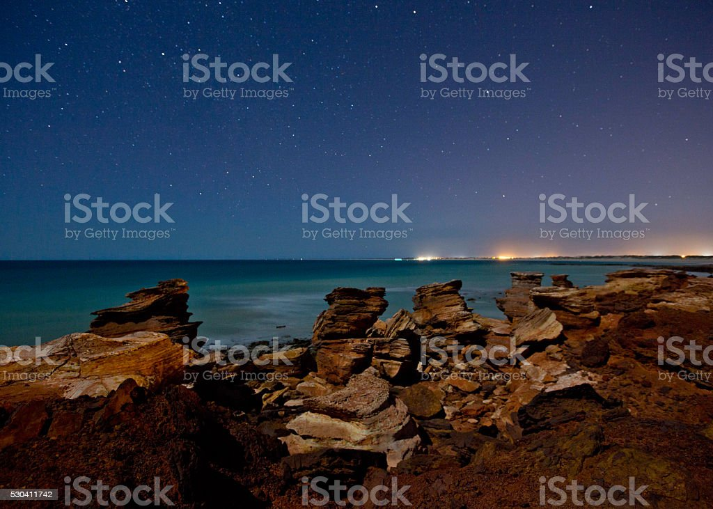 Rocky outcrop with aqua water and star filled sky stock photo