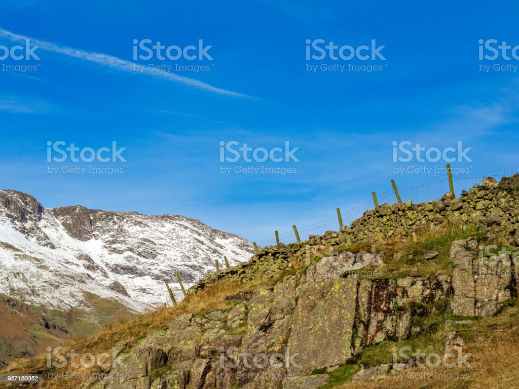 Rocky Outcrop with Fence and Snow covered Langdale Hills stock photo