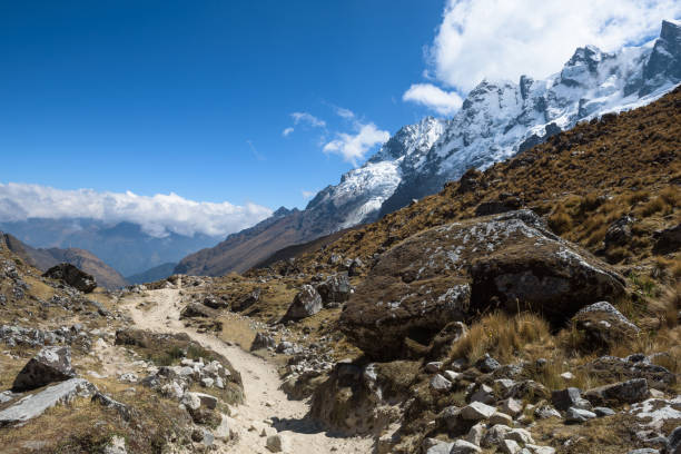 Rocky paths and green valleys surrounded by snowcapped mountains on the Salkantay Trek stock photo