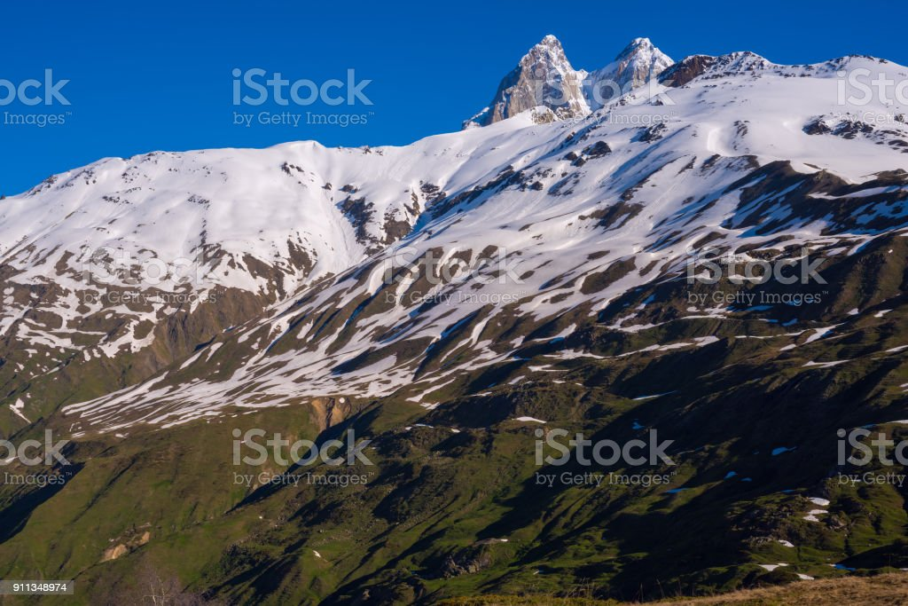 Rocky peaks of Ushba towering above the snow-covered ranges stock photo